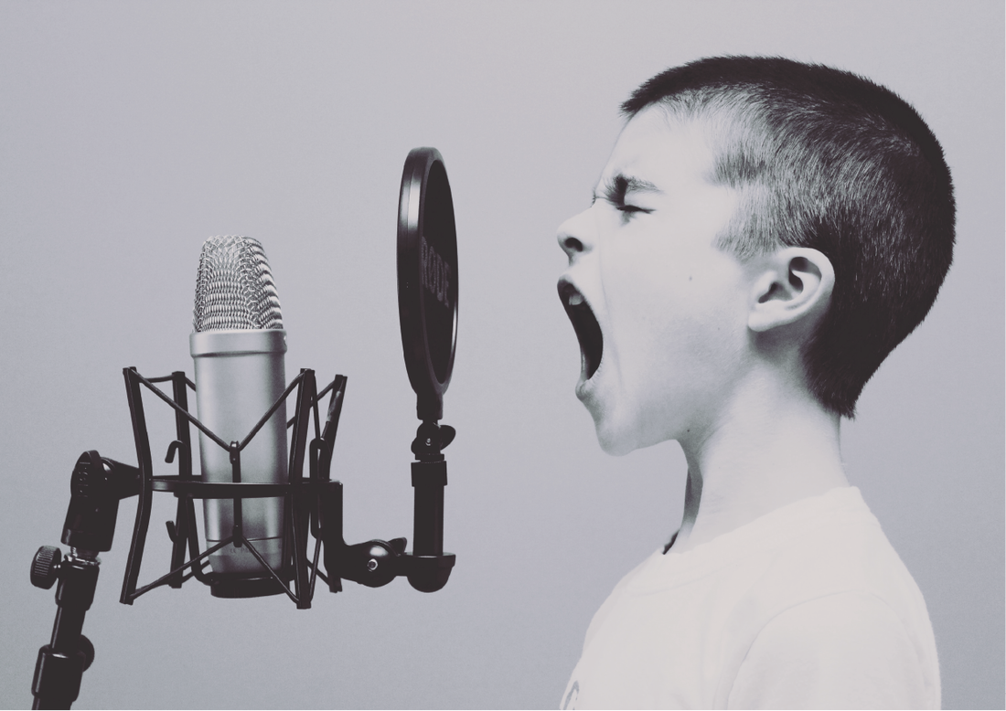 Boy yelling into microphone to promote newsletter